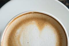 A metade do fim inferior de Flatlay acima da forma do coração espuma a arte do Latte do leite no copo de café branco fotografia de stock royalty free