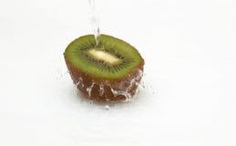 Metade do quivi suculento e da água limpa, fresca. Fotografia de Stock Royalty Free