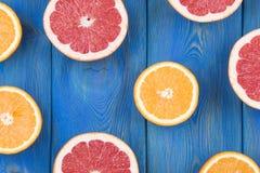 A metade fresca cortou a toranja e a laranja em um fundo de madeira azul Imagem de Stock