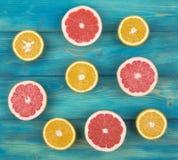 A metade fresca cortou a toranja e a laranja em um fundo de madeira azul Imagens de Stock Royalty Free