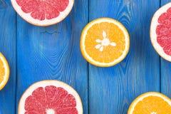 A metade fresca cortou a toranja e a laranja em um fundo de madeira azul Foto de Stock Royalty Free