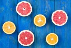 A metade fresca cortou a toranja e a laranja em um fundo de madeira azul Fotografia de Stock Royalty Free