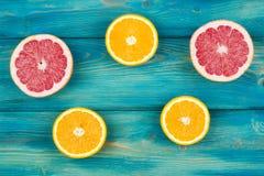 A metade fresca cortou a toranja e a laranja em um fundo de madeira azul Fotos de Stock