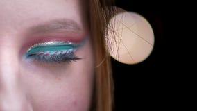Metade-retrato do modelo louro com a composição colorida que olha com sorriso flertando na câmera em luzes borradas filme