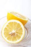 Metade suculenta de um limão no prato de cristal Fotos de Stock