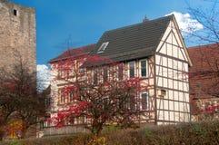 A metade suportou a casa perto da parede velha do castelo Imagens de Stock