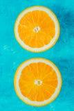 Metades da laranja na opinião superior do fundo ciano foto de stock royalty free