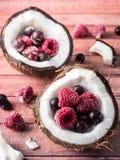 Metades do coco com bagas congeladas em um fundo de madeira escuro Fotografia de Stock Royalty Free