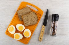 Metades dos ovos cozidos, pão na placa de corte, faca, frasco com o condimento na tabela de madeira Vista superior fotos de stock royalty free