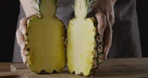 Metades maduras suculentas frescas do abacaxi orgânico natural nas mãos de uma mulher em uma placa de corte em uma tabela de made video estoque