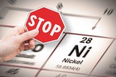 Metais pesados da parada - imagem do conceito com a mão que mantém um sinal da parada contra um elemento químico do níquel com o  fotografia de stock royalty free
