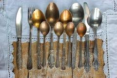 Metal łyżki, rozwidlenia, noże, na starym wieśniaka stole Zdjęcia Stock