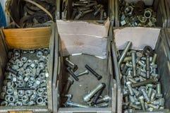 Metal śruby i stalowi rygle rozpraszali w pudełkach fotografia stock