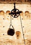 Metal ведро на смертной казни через повешение шкива в дворе, желтый фильтр Стоковая Фотография