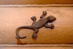 Metal вешалка с крюком в форме ящерицы на timbered w Стоковые Фотографии RF