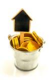 Metal ведро с золотыми монетками и деревянным домом Стоковые Фото