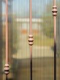 Metal выкованные загородка и листы просвечивающего коричневого поликарбоната Неясное изображение сада лета позади Стоковые Изображения RF