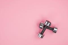 Metal гантели для поднятия тяжестей изолированного на розовой предпосылке Стоковое Изображение RF