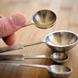 Metal измеряя ложки на деревянной разделочной доске зерна в кухне стоковое фото