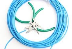 Metal инструменты и голубой кабель на белой предпосылке Стоковые Изображения