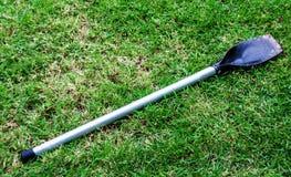 Metal короткий лопаткоулавливатель с деревянной ручкой на зеленой траве стоковое изображение