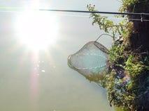 Metal клетка рыбной ловли пониженная в воду и отражение солнца в воде Фото было принято в сразу солнечный свет Стоковое Изображение
