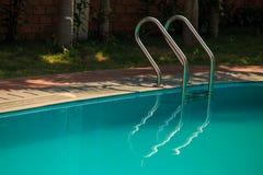 Metal лестница в бассейн от тротуара в месте ладони тенистом Стоковые Изображения RF