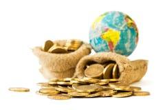 Metal монетки и глобус изолированные на белой предпосылке стоковые изображения
