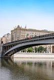 Metal мост через реку к городу, обваловка с домами Стоковое фото RF