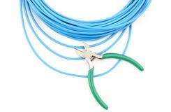 Metal острозубцы и голубой кабель на белой предпосылке Стоковая Фотография