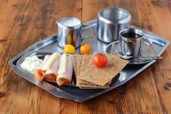 Metal поднос с crispbread, сыром, творогом, ветчиной, томатом вишни, чашкой кофе, опарником сахара, опарником creme на деревянном Стоковая Фотография