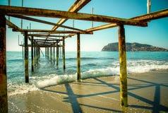 Metal пристань на пляже и красивый вид к древней крепости o Стоковое фото RF