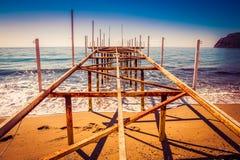 Metal пристань на пляже и красивый вид к древней крепости o Стоковые Изображения
