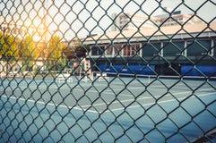 Metal проволочная изгородь сетки с теннисным кортом в расплывчатом для предпосылки стоковые фото