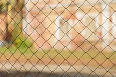 Metal плетение сетки на предпосылке запачканных зданий Стоковая Фотография RF