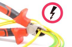 Metal плоскогубцы, зелен-желтый кабель и знак опасности высокого напряжения Стоковое Изображение
