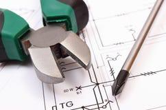Metal плоскогубцы и отвертка на электрическом чертеже конструкции дома Стоковое Фото