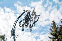 Metal символ Анжелы счастья семьи на улицах города против облачного неба Традиция смертной казни через повешение фиксирует новую Стоковое Изображение