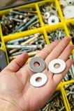 Metal шайба в руке на предпосылке инструментов стоковая фотография rf
