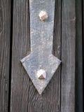 Metal шарнир с формой стрелки указывая вниз над старой дверью стоковая фотография