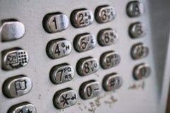 Metal шкала телефона в общественной телефонной будке с черными буквами и номерами на кнопках покрытых серебром стоковые фото
