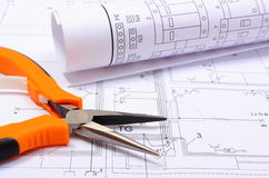 Metal плоскогубцы и свернутая электрическая диаграмма на чертеже конструкции дома Стоковая Фотография