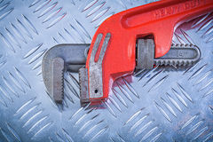 Metal adjustable monkey wrench on grooved metallic background co Royalty Free Stock Images