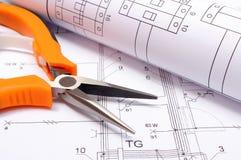 Metal alicates e o diagrama bonde rolado no desenho de construção da casa Fotografia de Stock