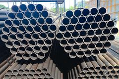 Metal and aluminium pipe heap in the cargo warehouse for transportation to the factory