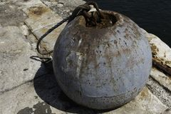 Metal anchor bell on a concrete wharf. Full view of a large old metal anchor bell sitting on a concrete pier royalty free stock image