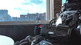 Metal android sitting at table in restaurant with glass of wine on background of view of high-rise buildings of city. Footage. Robot man behaves like human royalty free stock images