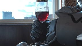 Metal android sitting at table in restaurant with glass of wine on background of view of high-rise buildings of city royalty free stock photography
