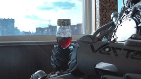 Metal android sitting at table in restaurant with glass of wine on background of view of high-rise buildings of city. Footage. Robot man behaves like human stock photo