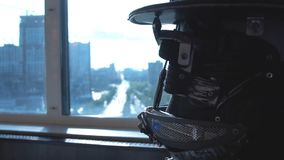 Metal android sitting at table in restaurant with glass of wine on background of view of high-rise buildings of city stock photo